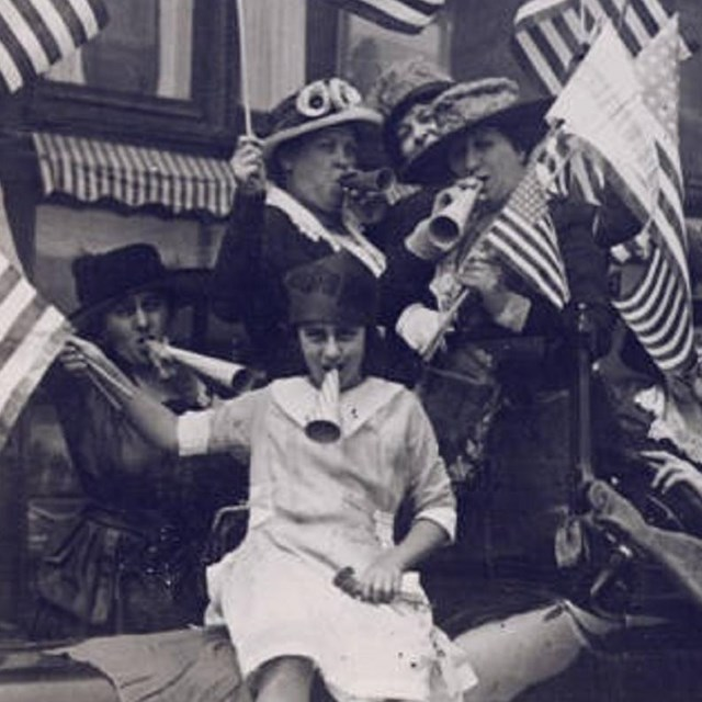 Women celebrating by waving American flags and blowing horns.