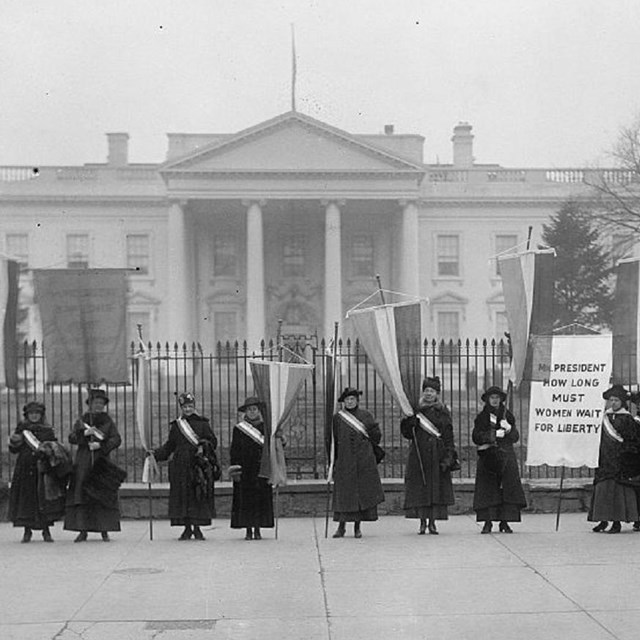 Black and white photo of suffragists holding flags and banners outside White House gates. LOC photo.