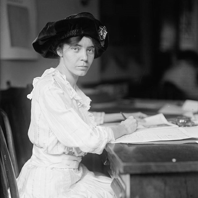 Alice Paul standing next to equality flag with stars. Courtesy of the Library of Congress.