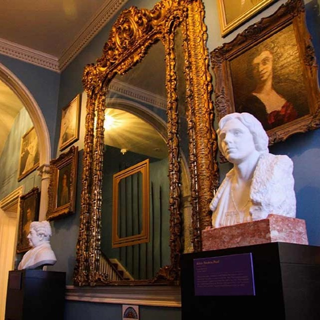 Interior of the entryway to the house with large mirror and busts. Courtesy National Woman's Party.
