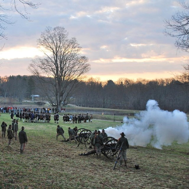 Men dressed in historical clothing firing cannons an a hillside at dusk. Courtesy NPS.