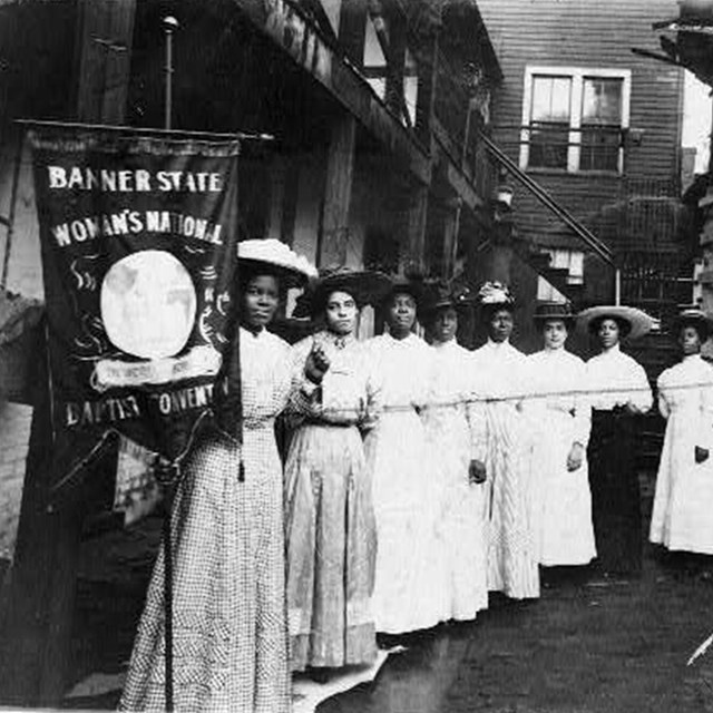 Nannie Helen Burroughs and other women holding a suffrage banner. LOC photo