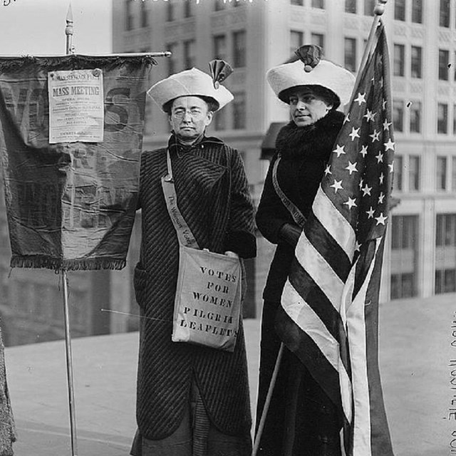 Group of women holding banners.