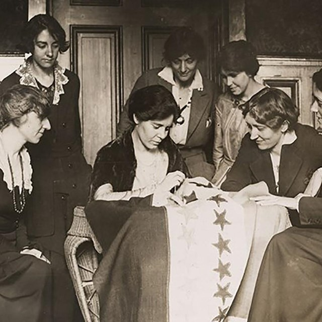 Alice Paul sews a star on the suffrage flag