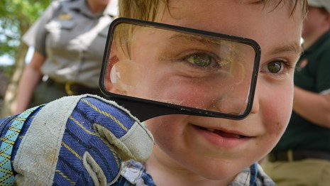 Face of a child with short blond hair looking closely through a magnifying glass at the camera.