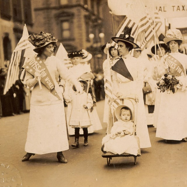 Suffragists marching in the street.