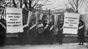 Suffragettes picket outside the White House fence.
