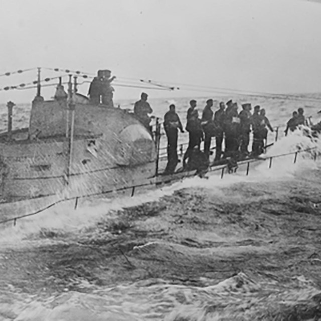 German submariners stand on the deck as waves crash around them.