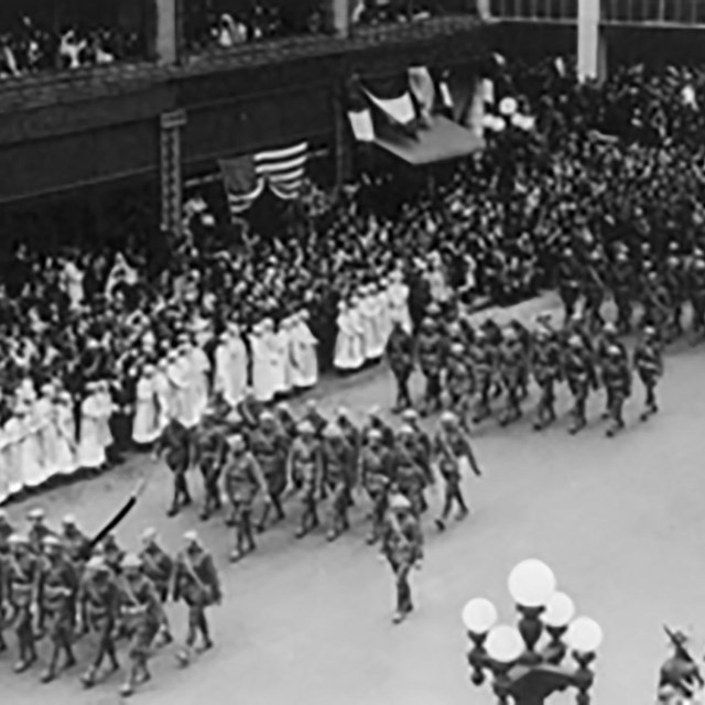 Soldiers march in a parade on a city street lined with spectators.