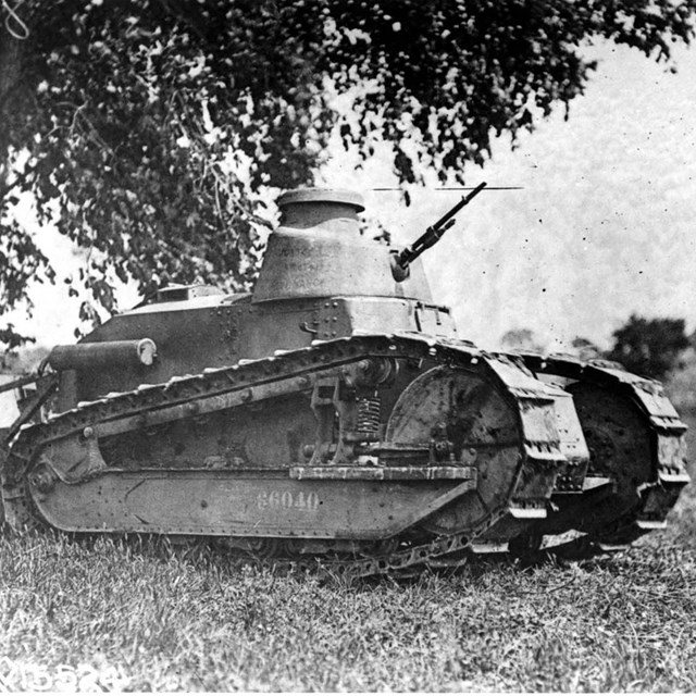 An army tank sits under a tree.