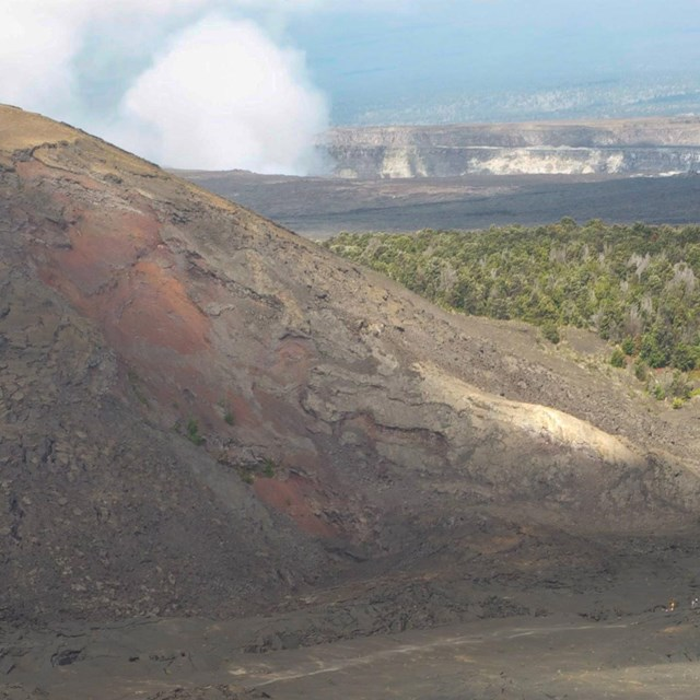 lava landscape in foreground with steam and greener hills in distance