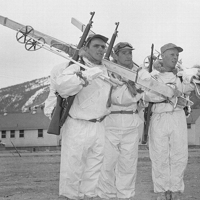 men pose in white suits with skis over their shoulders