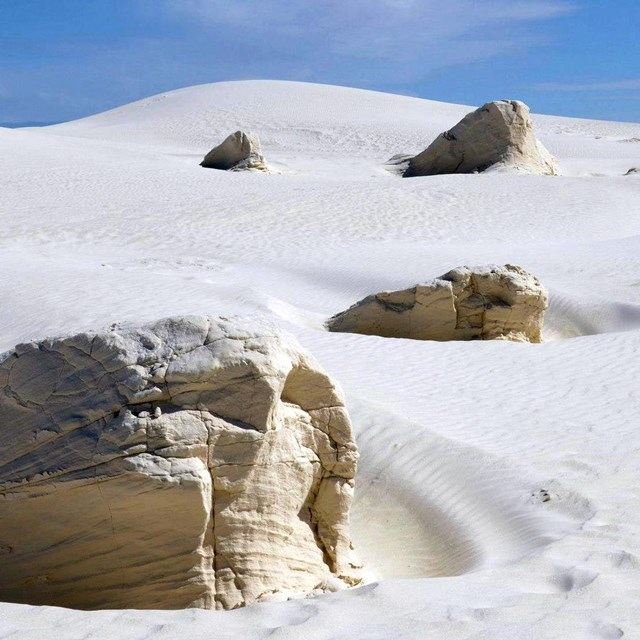 Rock in white sand dune with blue sky in distance