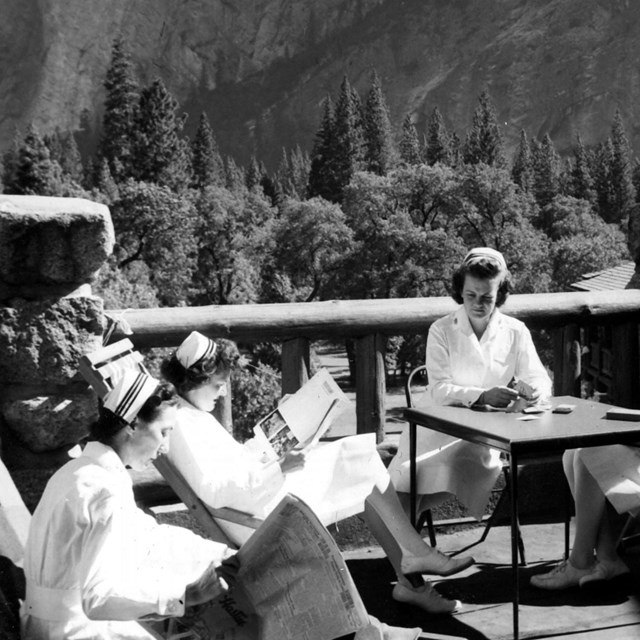 a nurse and sailors on patio; mountain in background