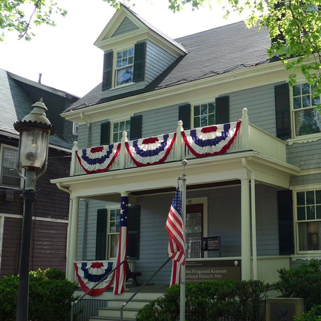a light blue new england style home with red white and blue bunting on second story porch