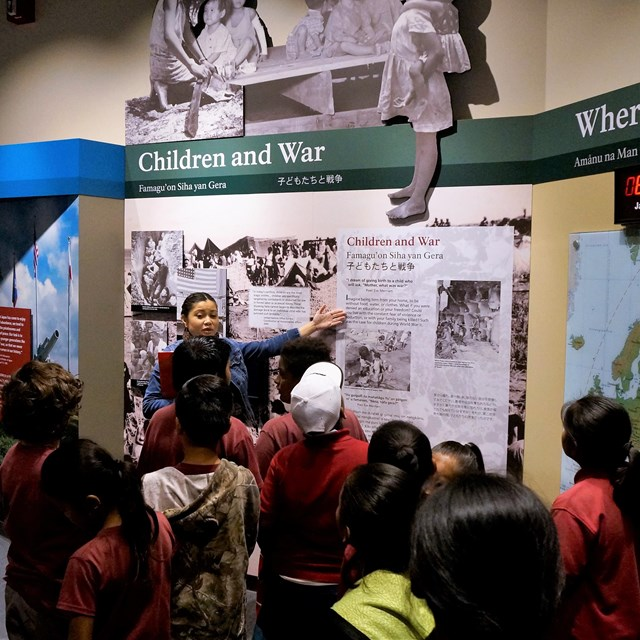 Ranger talking to a school group in front of an exhibit about children and war