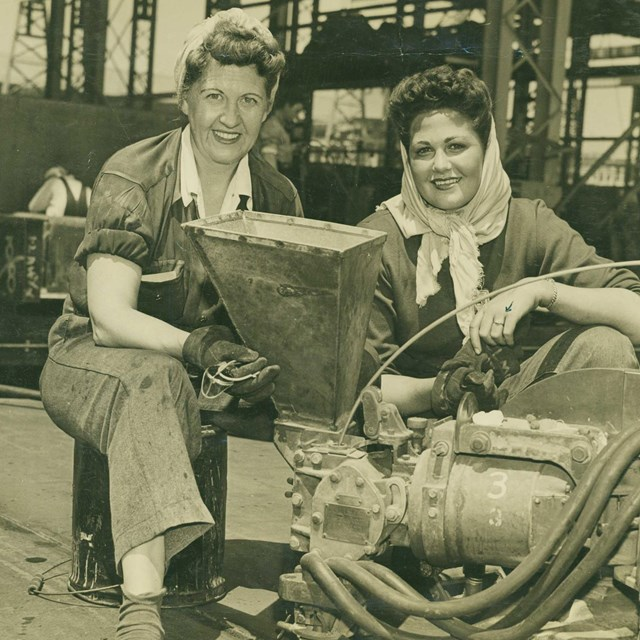 Two women in factory; black and white photo