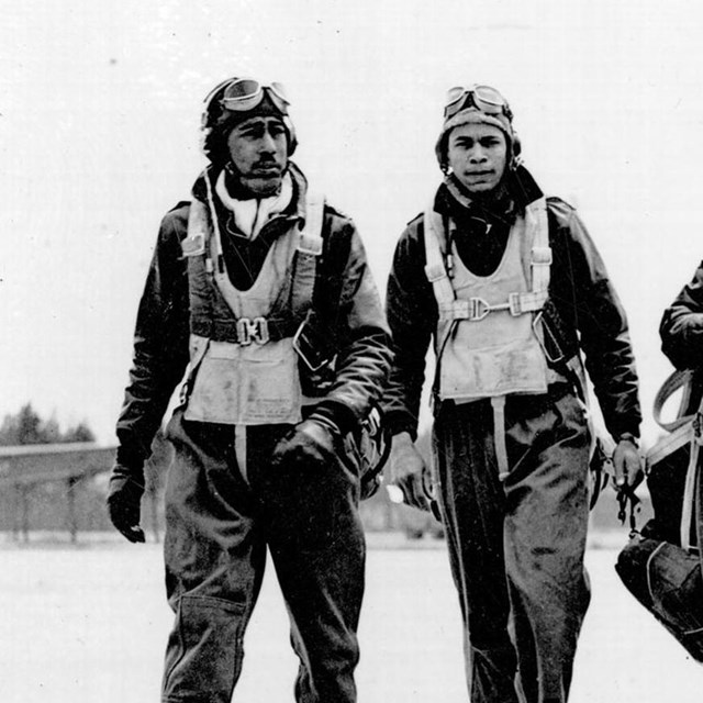 4 African American airmen walk down a runway; B&W photo