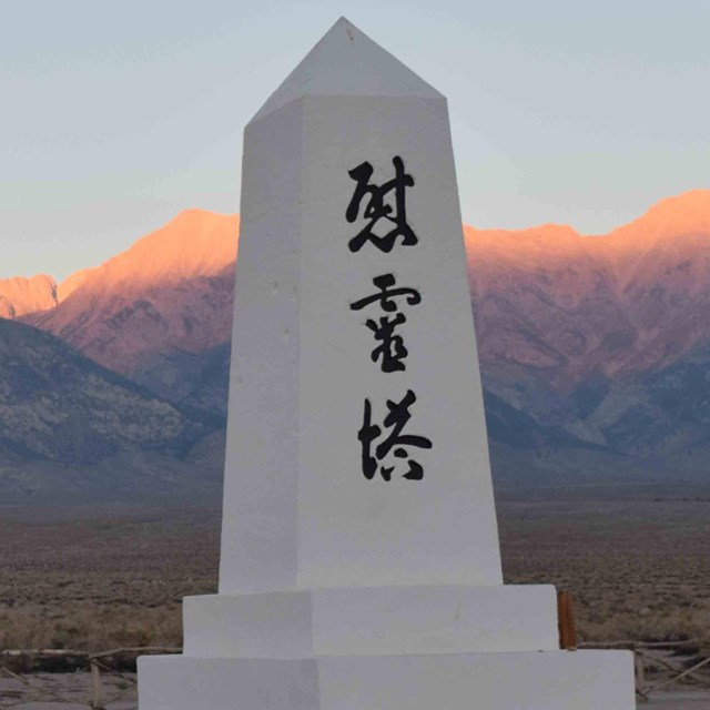 sunset next to a white monument with Japanese writing on it; mountains in background