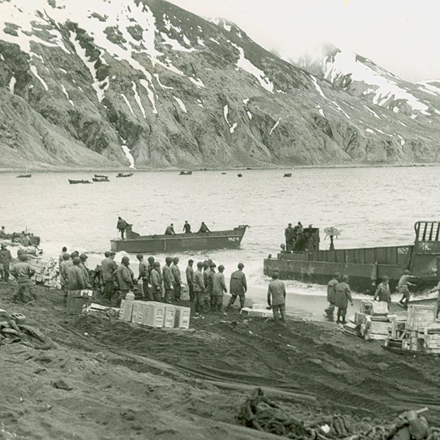 boats pull ashore, mountain in background, B&W photo