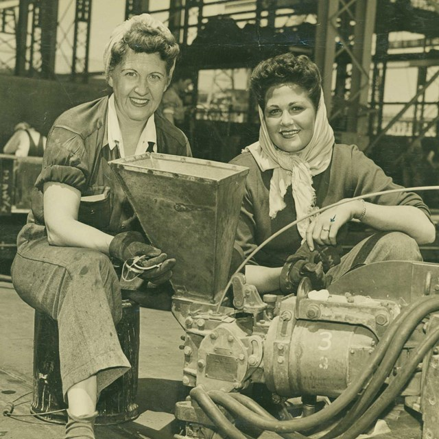 Two women in dungarees site in front of a machine