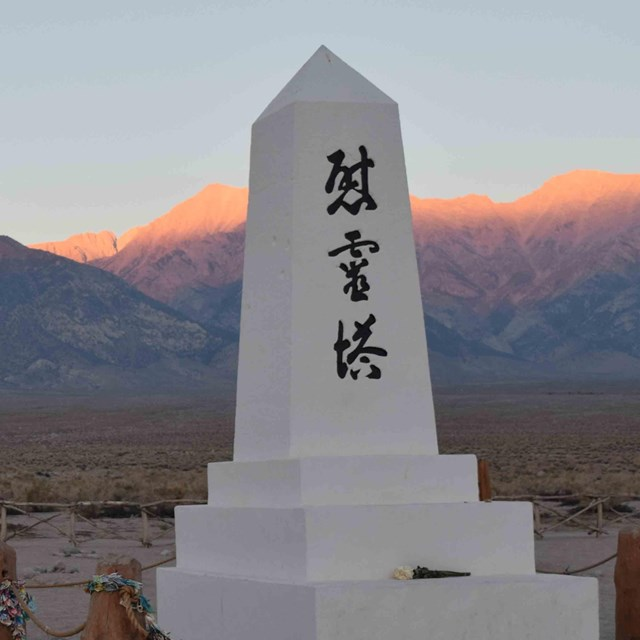sunset, an marble obelisk on the right with japanese characters