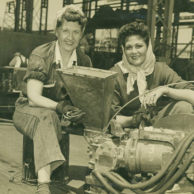 B&W photo of two women in overalls posing in a warehouse