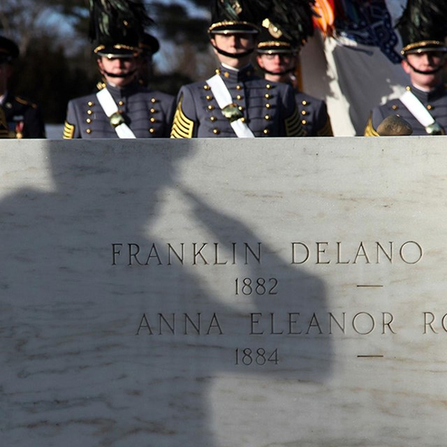 a shadow of a saluting soldier reflected on the marble grave of FDR