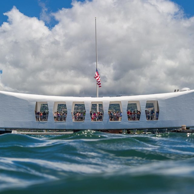 white bow shaped memorial seen from water level in the ocean