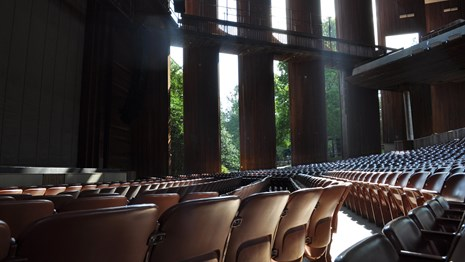 A view of front orchestra seats from a row facing the house right baffles with light shining through