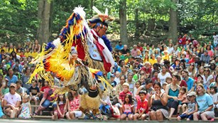 Native American in traditional dress dancing in front of an audience.