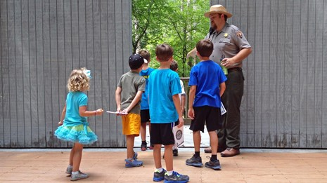 A ranger leads a program on stage with a group of children