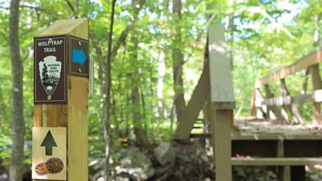 Wolf Trap Trail and TRACK Trail post marker with a bridge in the distance.