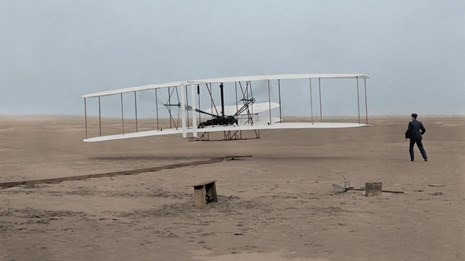 Early bi-wing airplane taking off in a field of sand