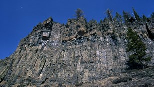 Brown and gray columns of rock make up a cliff that towers up to a deep blue sky.
