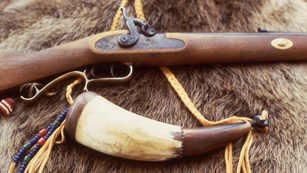 Rifle and powder horn with a map etched on side resting on fur.