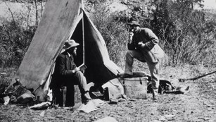 Man sits on a box in front of a canvas tent while another man stands next to him.