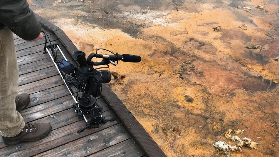 A camera mounted to a sliding apparatus resting on a wooden boardwalk.
