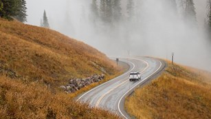 A car drives along on a winding road during a foggy morning.