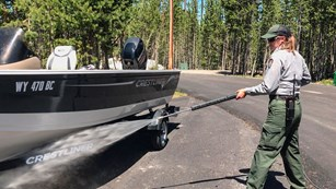 Photo of a park employee cleaning a boat with a power washer.