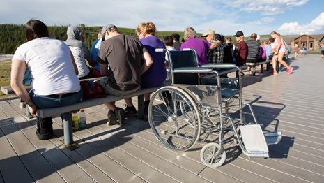 A wheelchair rests on the boardwalk behind a crowd of people sitting on benches.