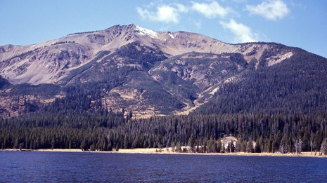 Tall mountain rises near the shore of an alpine lake.