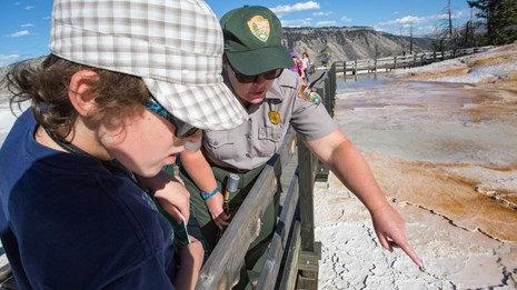 Interpretive ranger talks with a visitor while pointing out a hydrothermal feature.