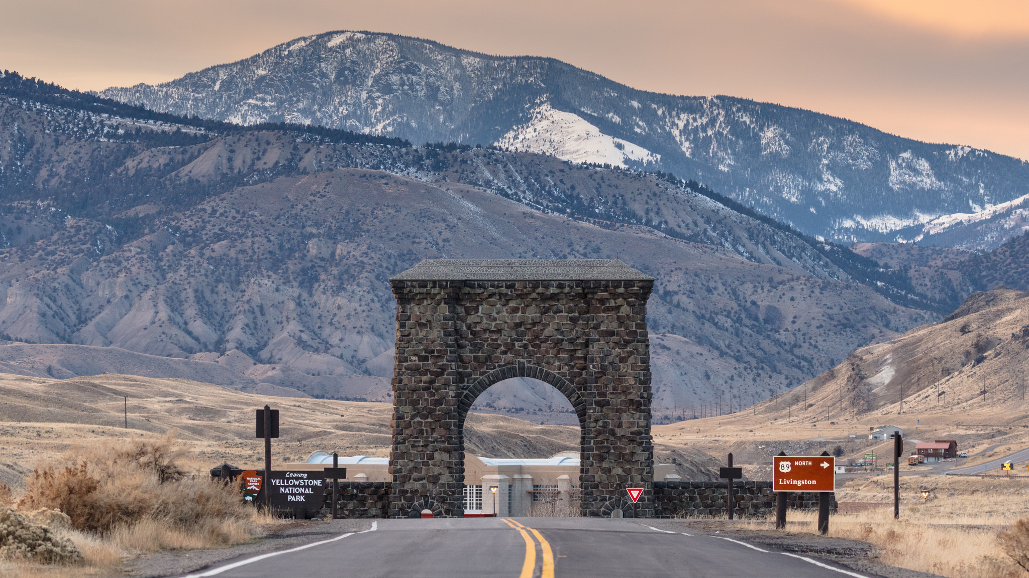 A brick arch with mountains with a mountainous background