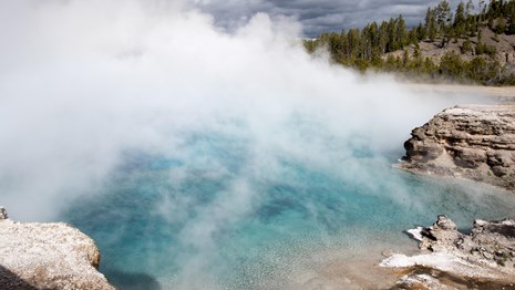 Steam rises from a blue pool down in a crater.