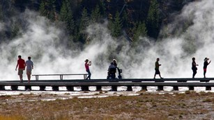 A visitor used a mobility aid to travel along the boardwalks at Midway Geyser Basin.