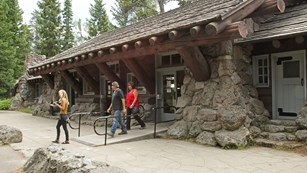 Three visitors leave the historic, one-story, stone and wood visitor center.