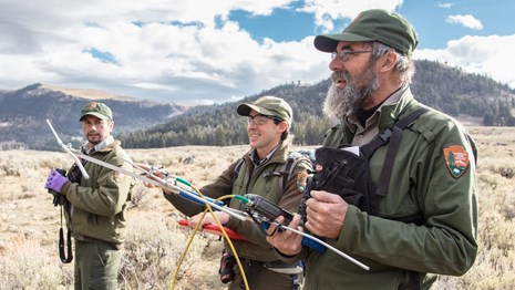 Three uniformed park employees testing telemetry gear in a meadow.