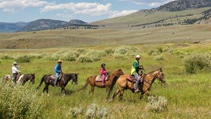 A line of horseback-riders travel across a sagebrush prairie.