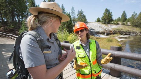 Ranger wearing a yellow safety vest talks with another ranger while standing on a bridge.